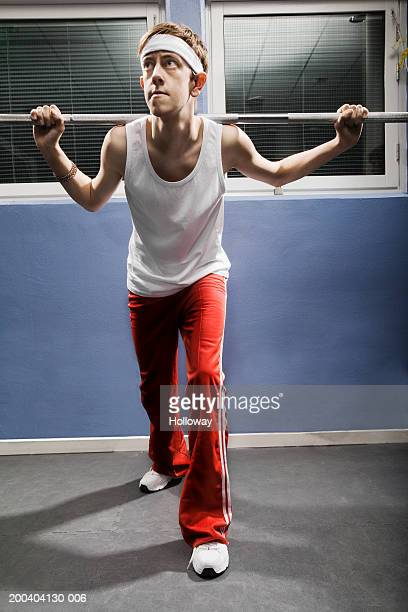Young man wearing sweatband lifting weight in gym
