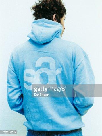 Young man wearing sweatshirt with hood, rear view : Stock Photo