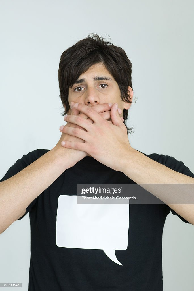 Young man wearing tee-shirt printed with blank word bubble, covering mouth with hands