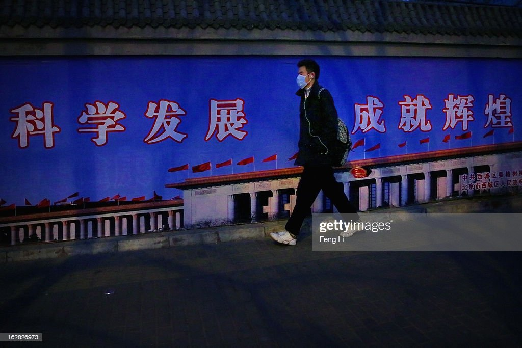 A young man wearing the mask walks along the wall with the picture of the Great Hall of the People during severe pollution on February 28, 2013 in Beijing, China. Beijing was hit by its first sandstorm of the year while its air quality reached dangerous level on Thursday.