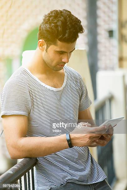 Young man wearing tracker in wrist and using digital tablet