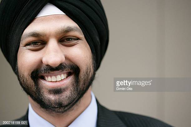 Young man wearing turban, smiling, close-up, portrait