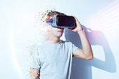 Young man wearing virtual reality goggles in modern coworking studio. Smartphone using with VR headset. Horizontal