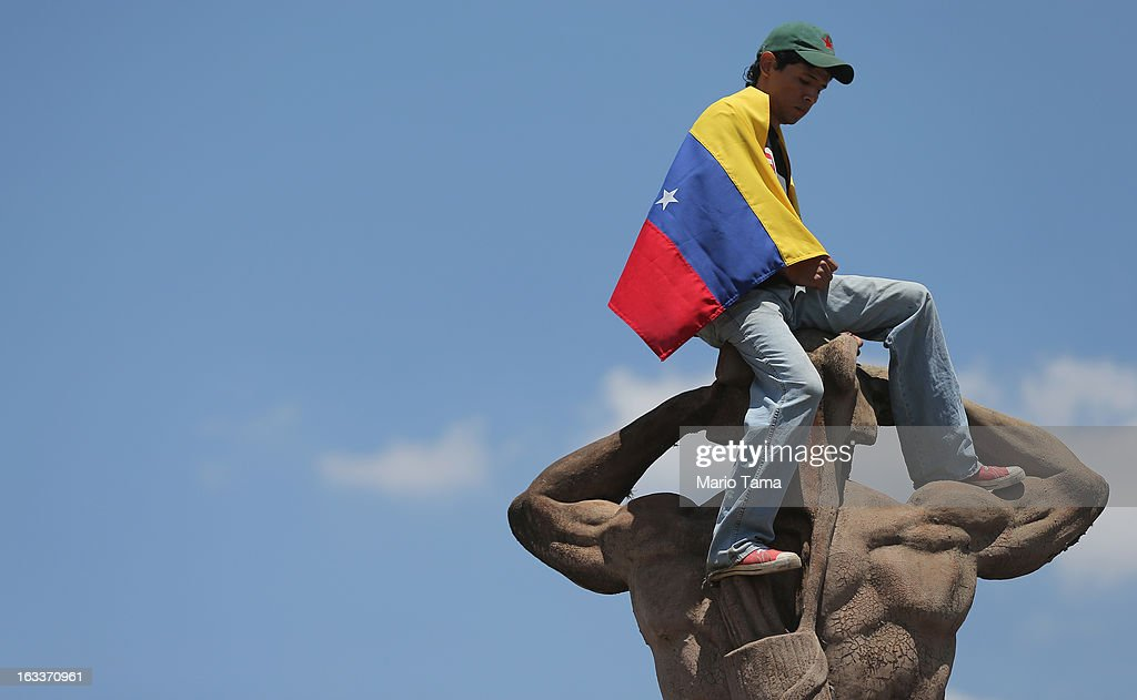 A young man wears a Venezuelan flag atop a statue outside the funeral for Venezuelan President Hugo Chavez at the Military Academy on March 8, 2013 in Caracas, Venezuela. Countless Venezuelans have paid their last respects to Chavez and more than 30 heads of state were expected to attend the funeral today.