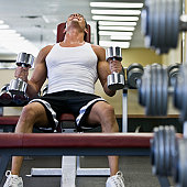 Young man weight training in gym