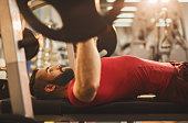 Young man weightlifting on a weight bench in gym.