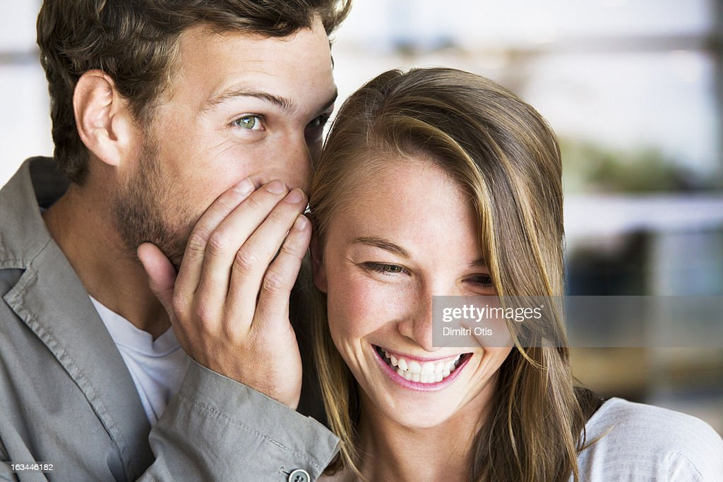 Young man whispers into young woman's ear : Stock Photo