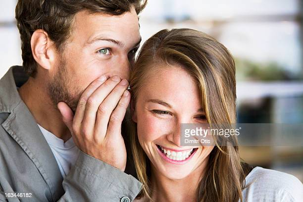 Young man whispers into young woman's ear
