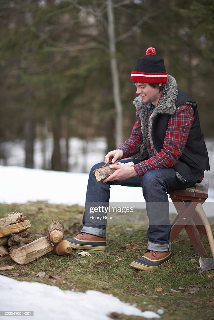 Young man whittling piece of firewood : Stock Photo