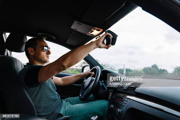 Young man who places the mirror in the car.