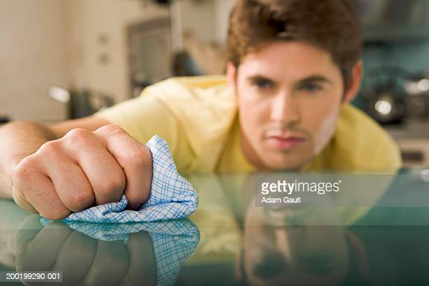 Young man wiping glass table with cloth (focus on hand and cloth)