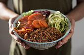 closeup of a young caucasian man with an appetizing buddha bowl in his hands, made with lentils, carrot, zucchini, lettuce and tomato