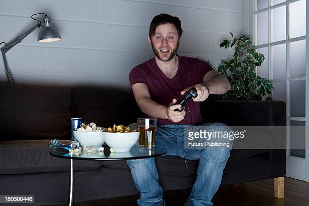 A young man with a cheerful expression playing Sony PlayStation 2 video games on a sofa alongside a table of snacks taken on July 9 2013