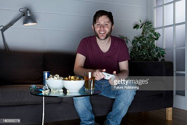 A young man with a cheerful expression playing XBox 360 video games on a sofa alongside a table of snacks taken on July 9 2013