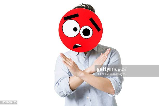 Young man with a confused emoticon face in front of his face