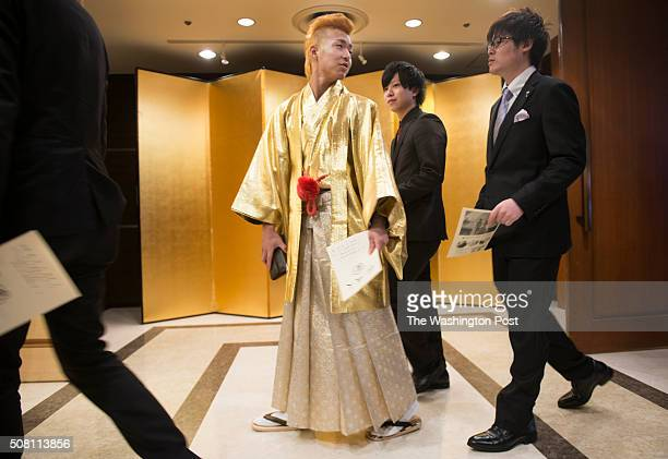 A young man with a gold mohawk in a hakama among others in business suits arrives at the Seijin no Hi ceremony in Kanazawa Japan on January 10 2016...