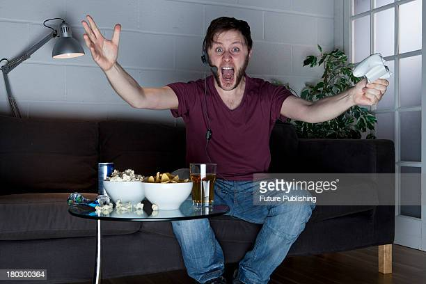 A young man with a headset shouting and gesturing at the television while playing XBox 360 video games on a sofa alongside a table of snacks taken on...