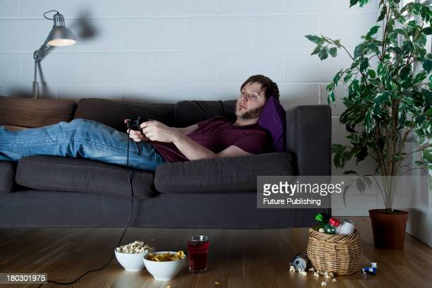 A young man with a sleepy expression playing Sony PlayStation 2 video games while lying on a sofa with bowls of snacks taken on July 9 2013