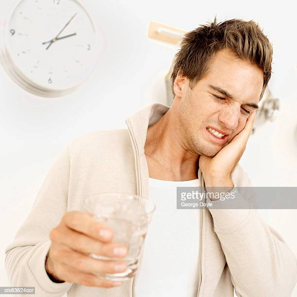 young man with a toothache due to cold water