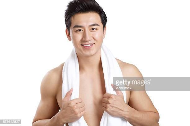 A young man with a towel on his shoulder
