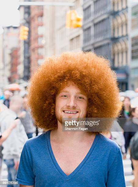 Young Man With Afro Standing on City Sidewalk