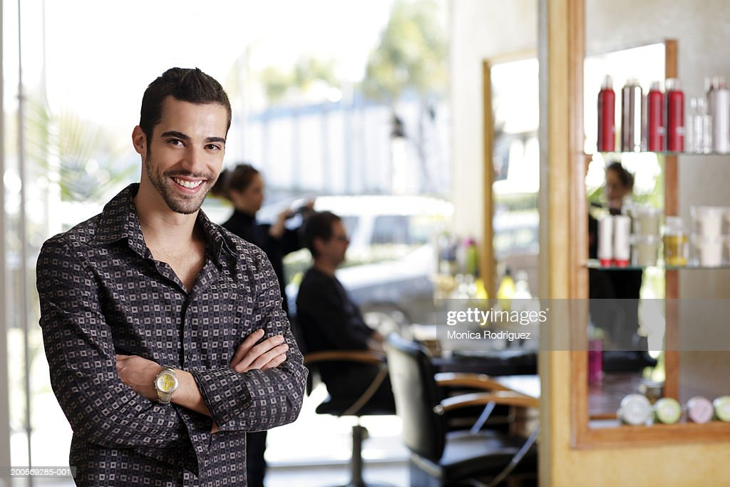Young man with arms crossed, portrait, hair salon in background : Stock Photo