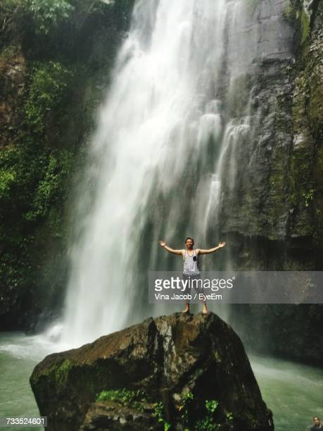 Young Man With Arms Outstretched Standing On Rock Against Waterfall