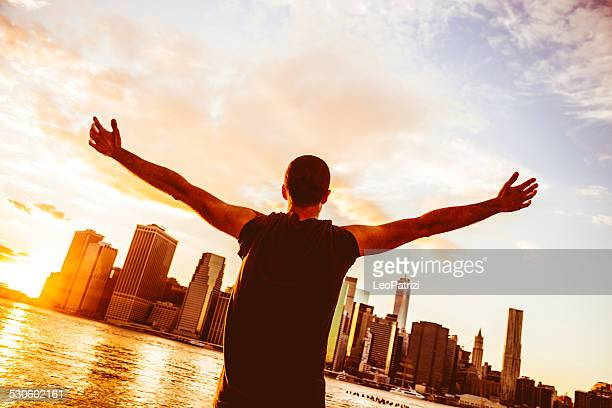 Young man with arms raised in front of the skyline