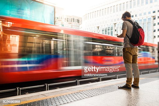 Young man with backpack and headphones waiting for train