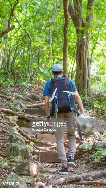Young Man with Backpack Trekking in Rainforest