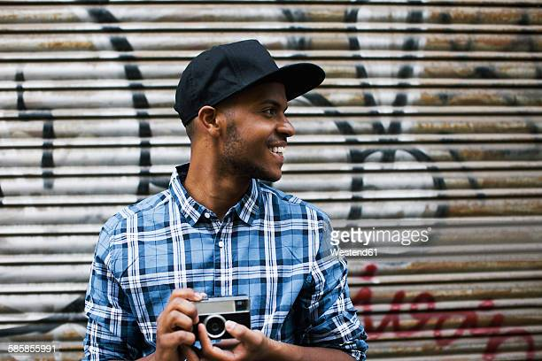 Young man with baseball cap and camera in front of roller shutter