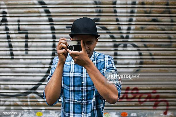Young man with baseball cap taking photos in front of roller shutter