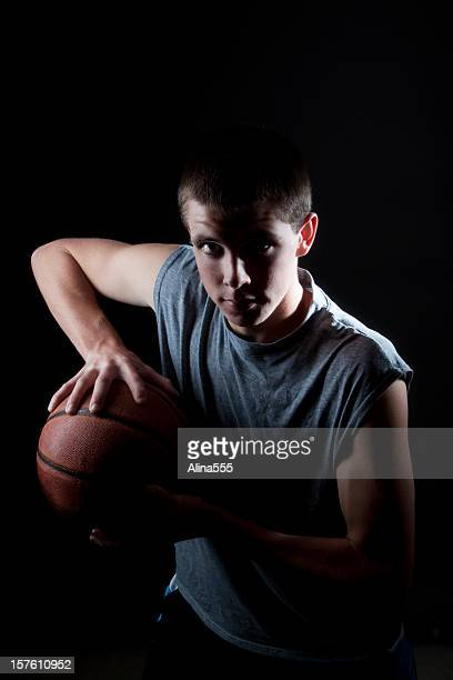Young man with basketball on black background