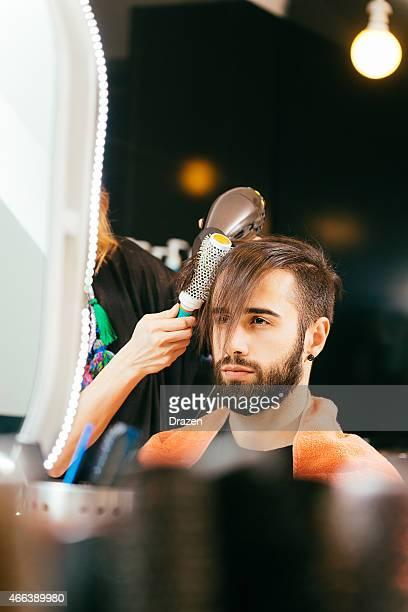 Giovane uomo con la barba in parrucchieri faning i suoi Capelli castani