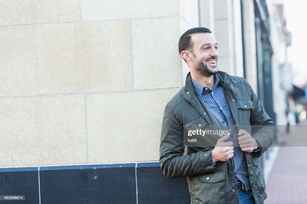 Young man with beard standing on city street corner : Foto stock