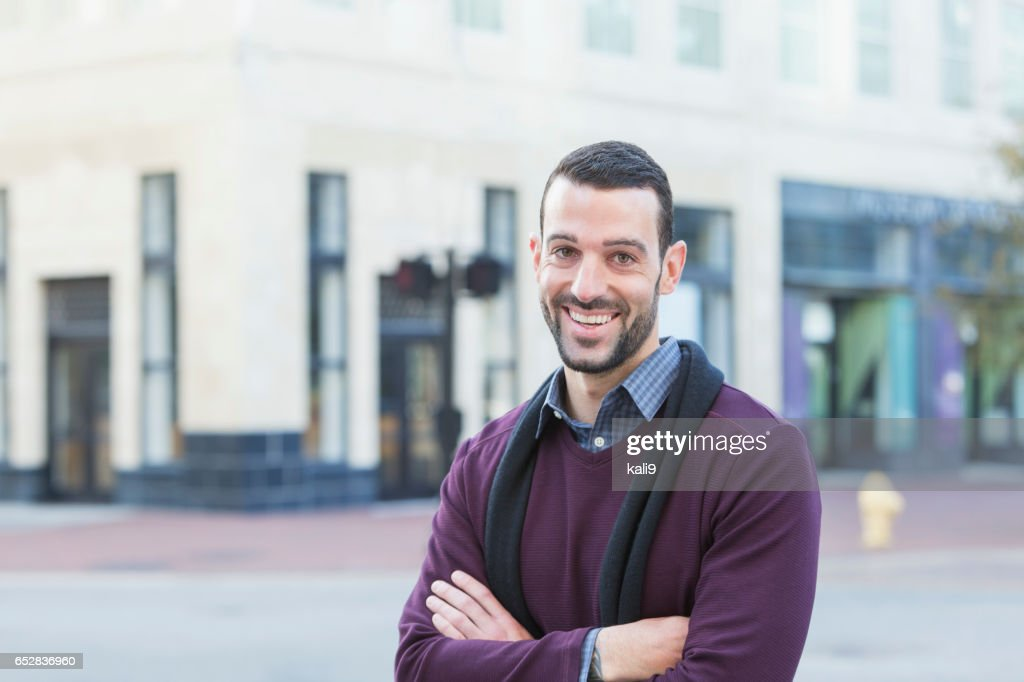 Young man with beard standing on city street corner : Stock Photo