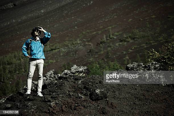 young man with binoculars in the mountain