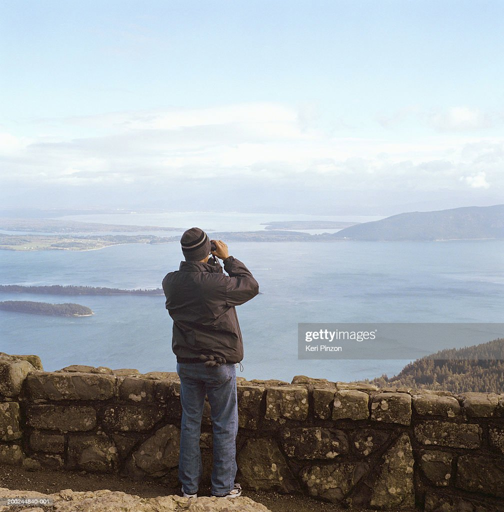 Young man with binoculars looking out over water, rear view