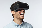Young man with bristle in blue shirt, wearing virtual reality glasses, lauthing at loud, looking to the right, enjoying watching 3d movie in vr headset