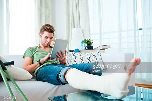 Junger Mann mit einem gebrochenen Bein wie zu Hause fühlen.