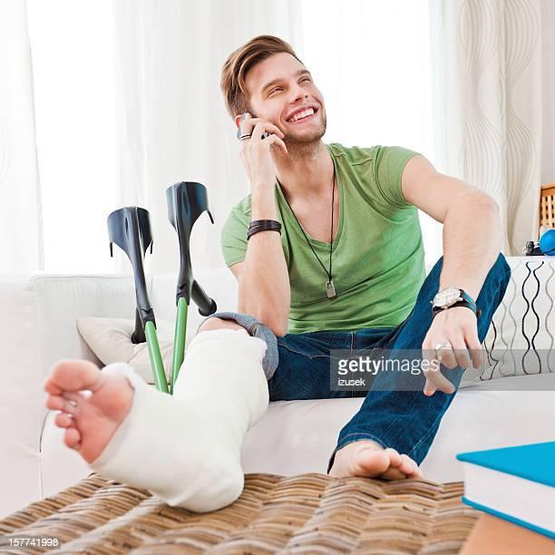 Hombre joven con pierna fracturada en su casa