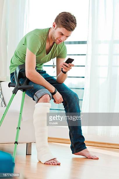 Young man with broken leg at home