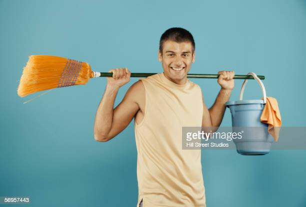 Young man with broom and bucket