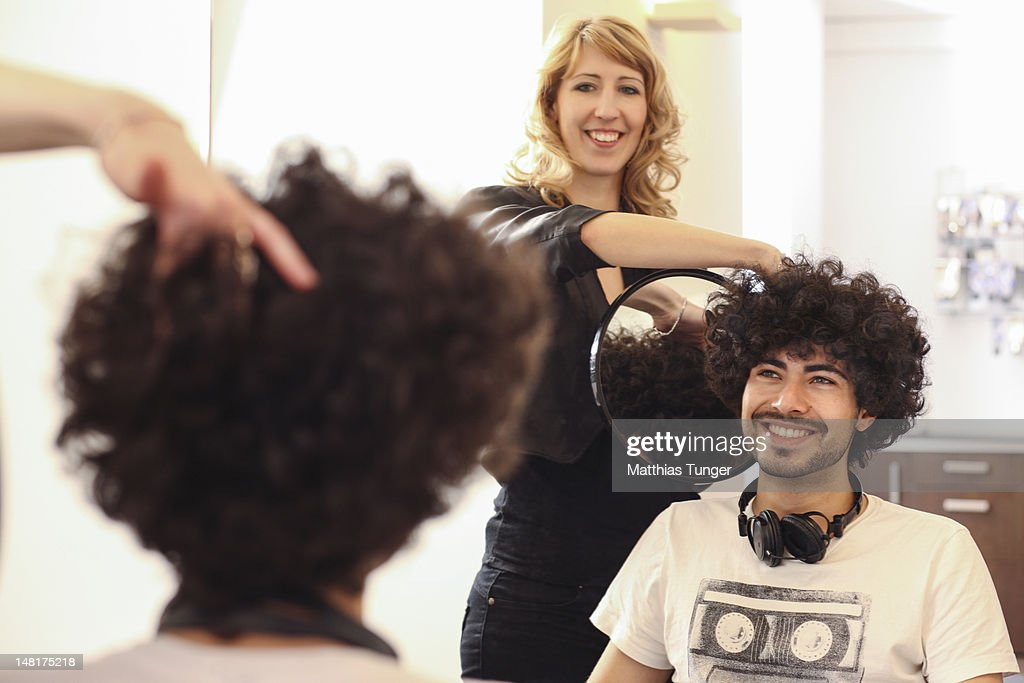 young man with buckled hair and hairdresser : Stock Photo