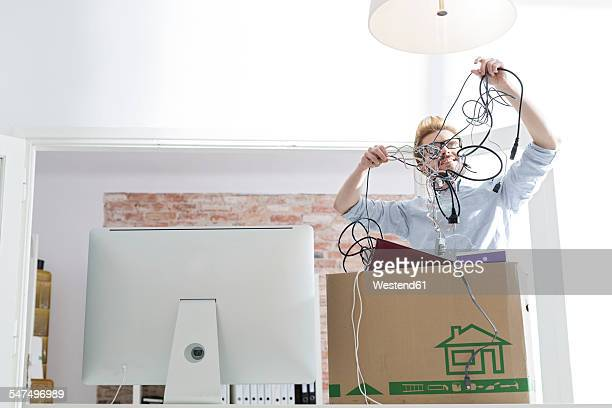Young man with cable tangle in office