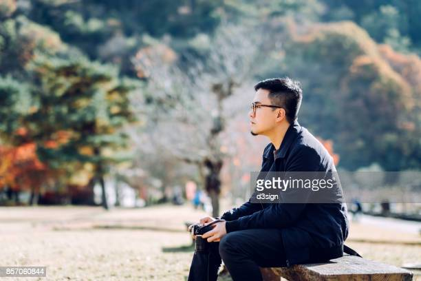 Young man with camera resting on park bench enjoying the Autumn foliage in a nature park
