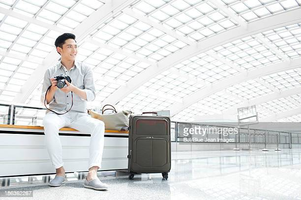 Young man with camera waiting at the airport