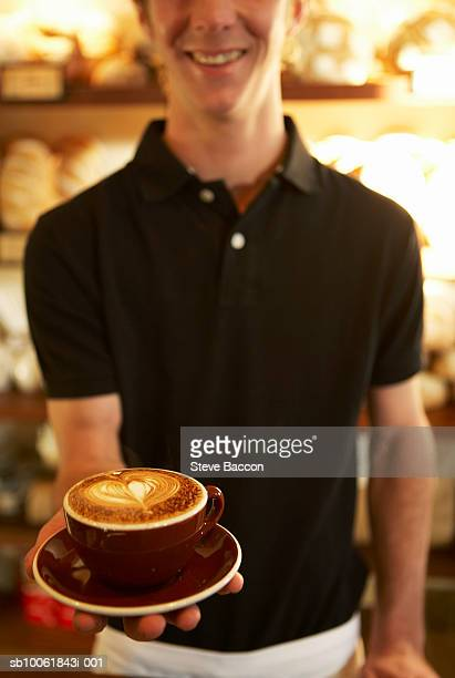 Young man with cappuccino cup, mid section