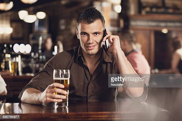 Jeune homme avec téléphone portable et de la bière