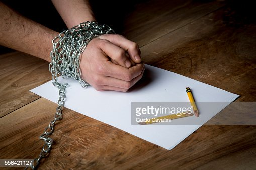 Young man with chains wrapped around his wrists, paper and broken pencil in front of him, focus on hands